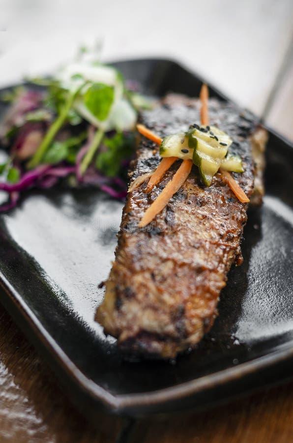 Μαριναρισμένο ψημένο στη σχάρα πλευρό χοιρινού κρέατος σχαρών με τη σαλάτα στοκ εικόνες με δικαίωμα ελεύθερης χρήσης