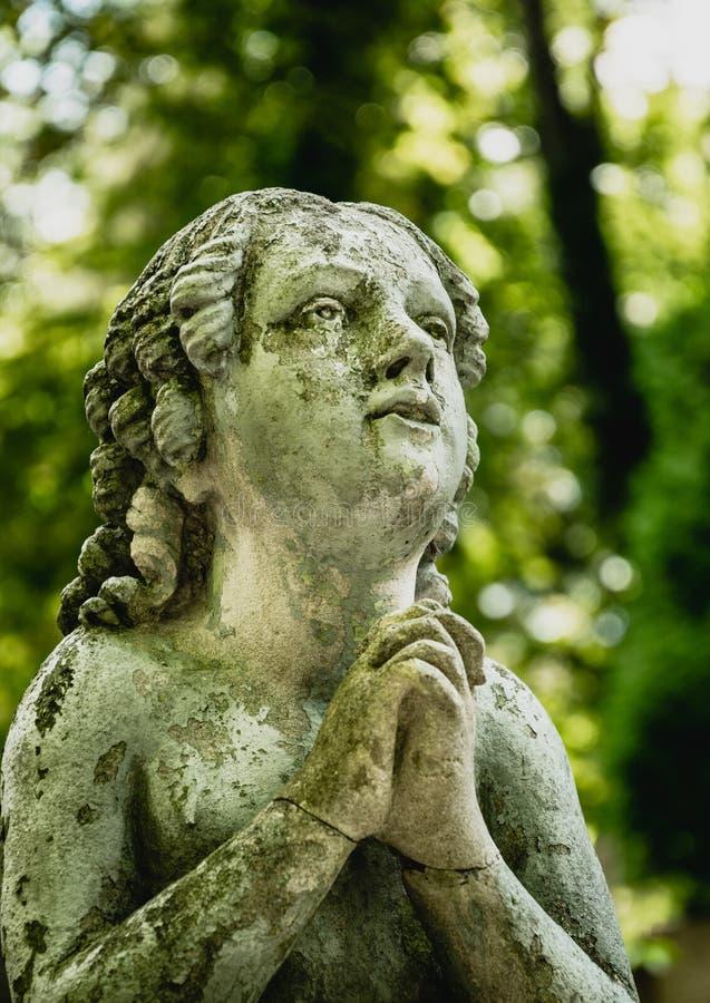 Μαρμάρινο άγαλμα και ένα αρχαίο εγκαταλειμμένο γοτθικό νεκροταφείο στοκ φωτογραφία