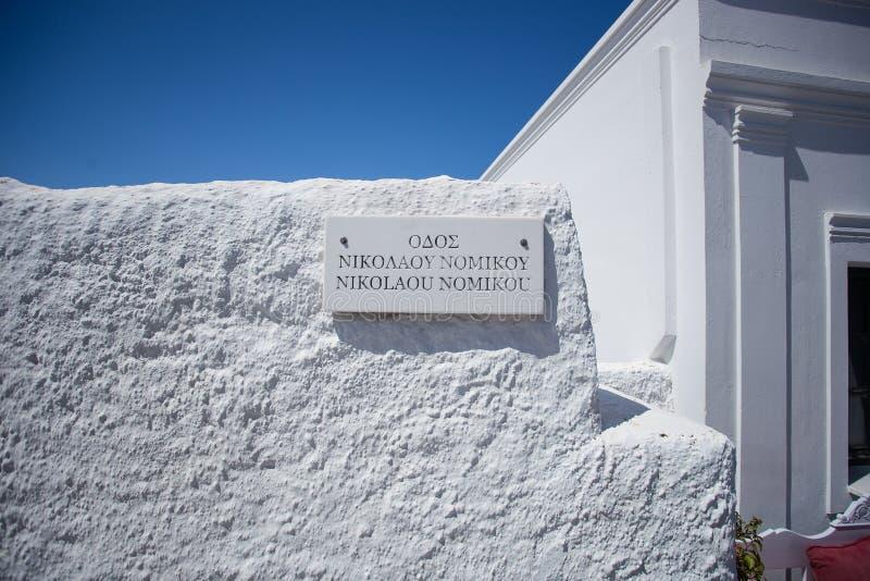 Μαρμάρινο σημάδι στα ελληνικά, στον παραδοσιακό άσπρο πλυμένο τοίχο που λούζεται από το φως και τη σκιά στο παραδοσιακό σπίτι San στοκ φωτογραφία με δικαίωμα ελεύθερης χρήσης