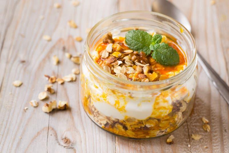 Μαρμελάδα γιαουρτιού, granola και λευκαγκαθιών στο βάζο γυαλιού στοκ εικόνες