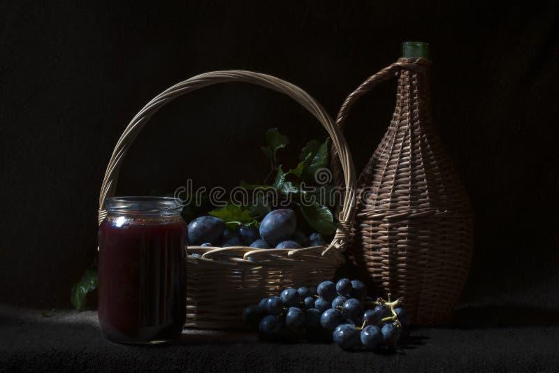 Μαρμελάδα, δαμάσκηνα, σταφύλια και καλάθια στοκ εικόνες