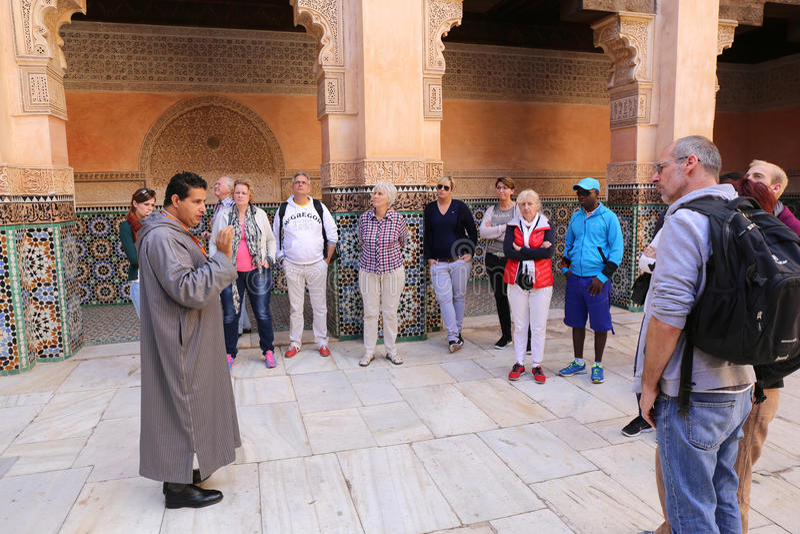 Μαροκινός οδηγός τουριστών που δίνει τις πληροφορίες για το παλάτι στους γερμανικούς τουρίστες στοκ φωτογραφίες
