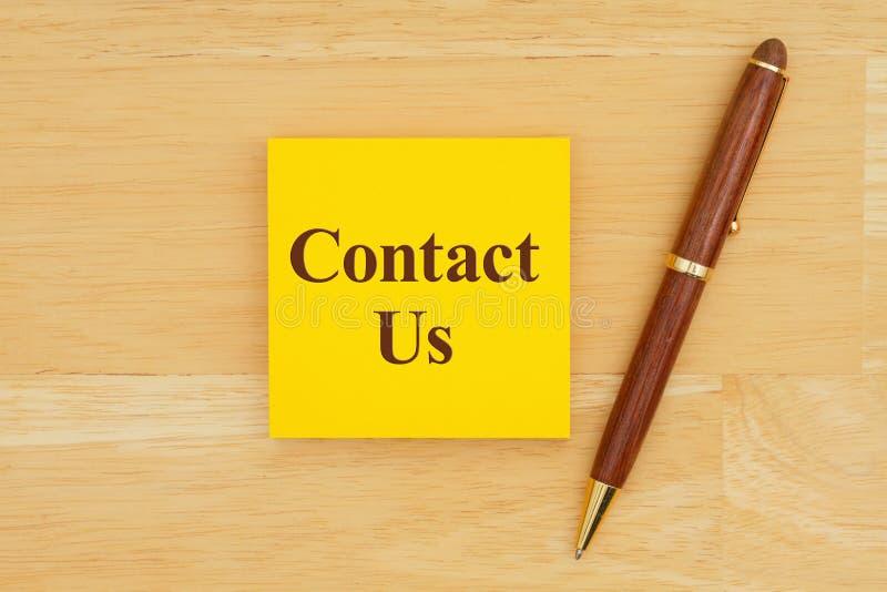 Μας ελάτε σε επαφή με μήνυμα στην κολλώδη σημείωση με μια μάνδρα στο κα στοκ φωτογραφίες