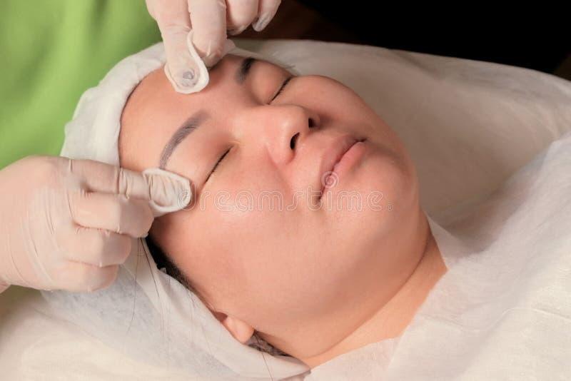 Μασάζ προσώπου Cosmetological διαδικασία Rejuvenating για μια μουσουλμανική γυναίκα Τα χέρια ενός beautician στα άσπρα γάντια βάζ στοκ εικόνα με δικαίωμα ελεύθερης χρήσης