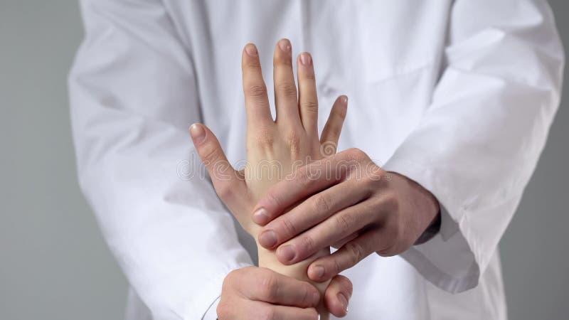 Μασέρ που δίνει το υπομονετικό μασάζ χεριών μετά από τον τραυματισμό, που εξετάζει τον καρπό ασθενών στοκ εικόνες
