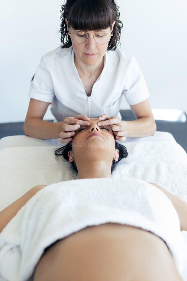 Μασέρ που κάνει το θεραπευτικό μασάζ προσώπου στη νέα έγκυο γυναίκα στο κέντρο SPA στοκ φωτογραφία