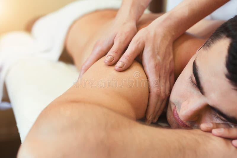 Μασέρ που κάνει το μασάζ ώμων στο σώμα ατόμων στοκ φωτογραφία με δικαίωμα ελεύθερης χρήσης