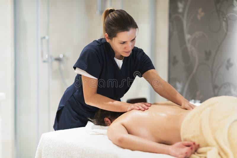 Μασέρ που τρίβει το λαιμό και τα sholders του πελάτη στοκ φωτογραφία με δικαίωμα ελεύθερης χρήσης