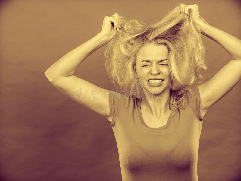 Ματαιωμένη γυναίκα που κρατά τη χαλασμένη ξανθή τρίχα της στοκ φωτογραφία με δικαίωμα ελεύθερης χρήσης