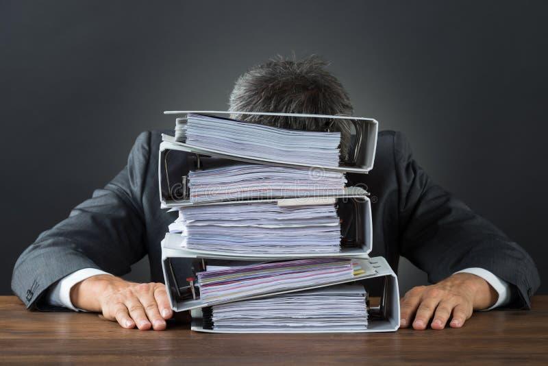 Ματαιωμένος επιχειρηματίας με το μέρος των αρχείων στο γραφείο στοκ εικόνες