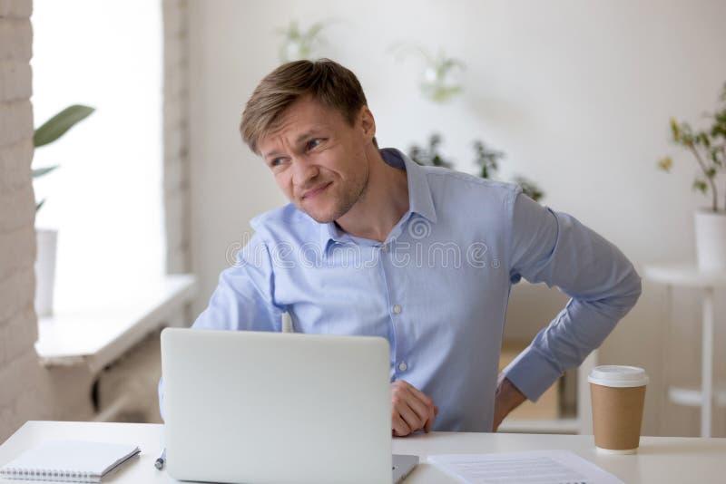Ματαιωμένος επιχειρηματίας που πάσχει από τον πόνο στην πλάτη στον εργασιακό χώρο στοκ εικόνες