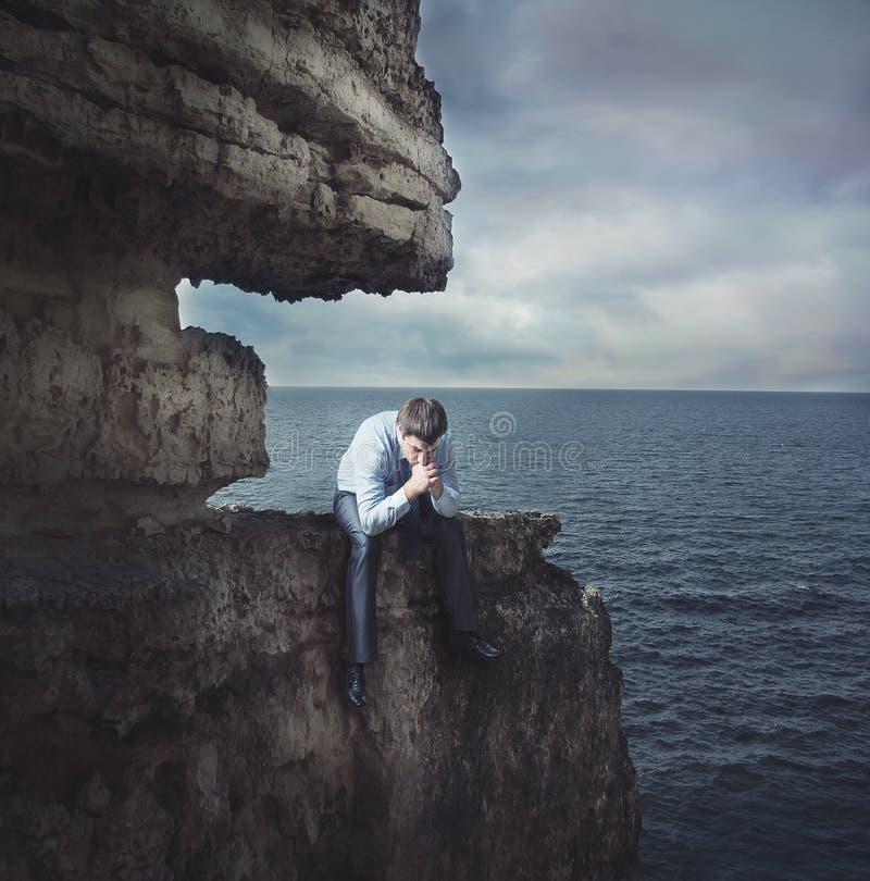 Ματαιωμένος επιχειρηματίας στον απότομο βράχο στοκ φωτογραφία με δικαίωμα ελεύθερης χρήσης