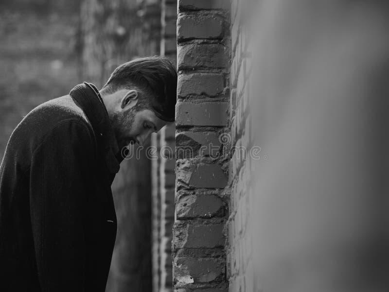 Ματαιωμένος καταθλιπτικός νεαρός άνδρας κοντά στο τουβλότοιχο που φαίνεται Λυπημένο τονισμένο δραματικό πορτρέτο κινηματογραφήσεω στοκ φωτογραφία με δικαίωμα ελεύθερης χρήσης