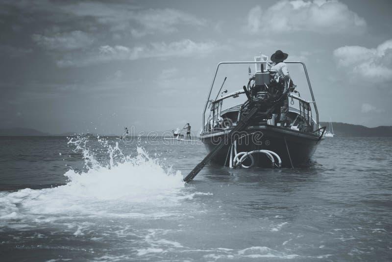 Ματ που τονίζεται γραπτός Ο οδηγός motorboat longtail οδηγεί μια μηχανή με μια μακροχρόνια κίνηση και έναν προωστήρα Ναυτικός στο στοκ εικόνα με δικαίωμα ελεύθερης χρήσης