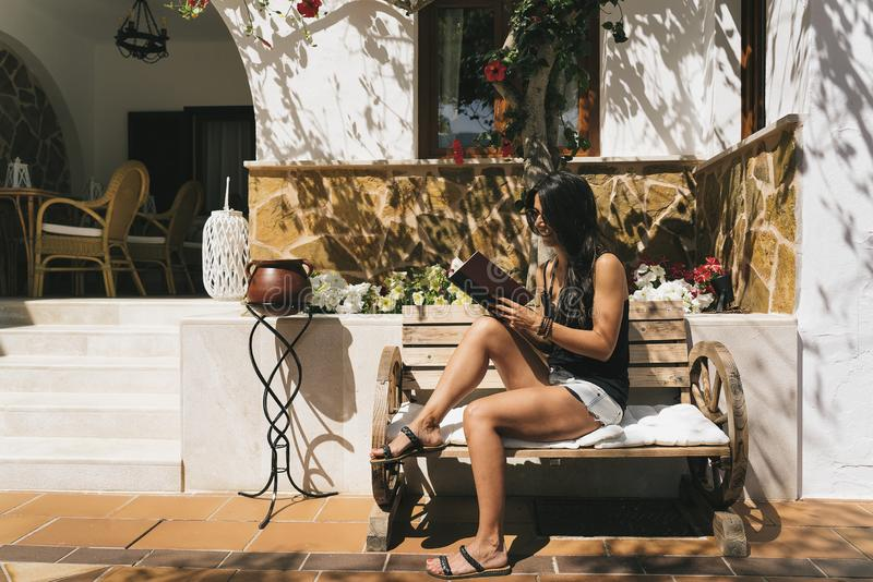 Μαυρισμένη γυναίκα που διαβάζει ένα βιβλίο σε έναν πάγκο οδών σε μια ηλιόλουστη ημέρα σε Majorca στοκ φωτογραφία με δικαίωμα ελεύθερης χρήσης