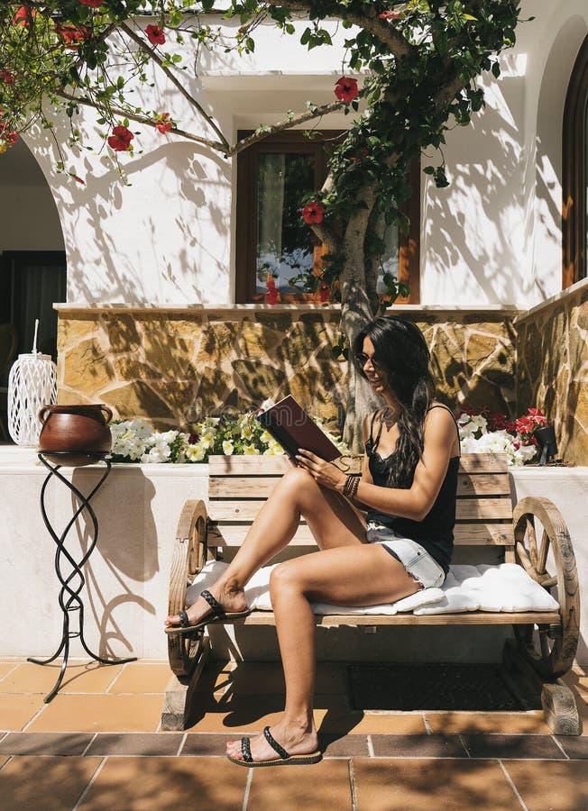 Μαυρισμένη γυναίκα που διαβάζει ένα βιβλίο σε έναν πάγκο οδών σε μια ηλιόλουστη ημέρα σε Majorca στοκ εικόνα με δικαίωμα ελεύθερης χρήσης