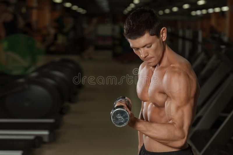 Μαυρισμένο μυϊκό άτομο workout με τους αλτήρες στη γυμναστική στοκ εικόνα