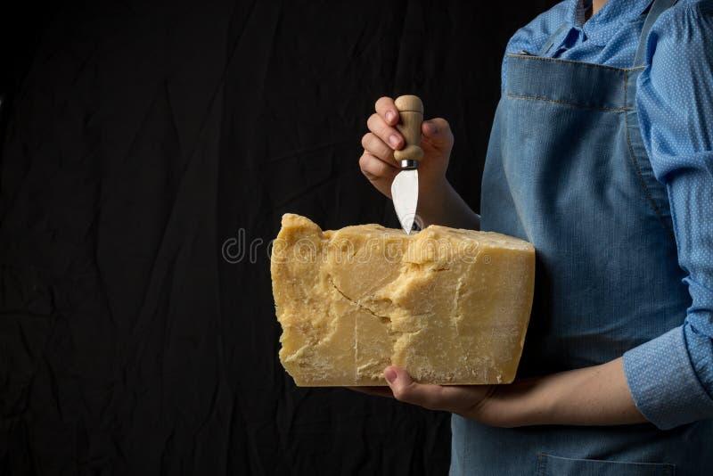 Μαχαίρι εκμετάλλευσης γυναικών και μια φέτα του τυριού παρμεζάνας στο μαύρο υπόβαθρο στοκ εικόνα με δικαίωμα ελεύθερης χρήσης