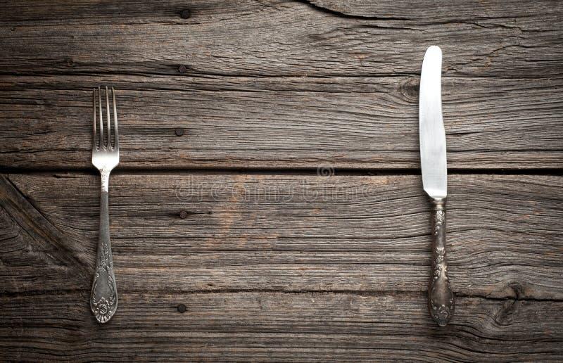 Μαχαίρι και δίκρανο στο ξύλινο υπόβαθρο στοκ φωτογραφία