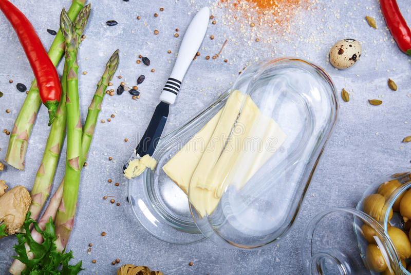 Μαχαίρι και ανθρακόπλινθος της μαργαρίνης Βούτυρο σε ένα κιβώτιο γυαλιού και λαχανικά σε ένα επιτραπέζιο υπόβαθρο Υγιής προετοιμα στοκ εικόνες