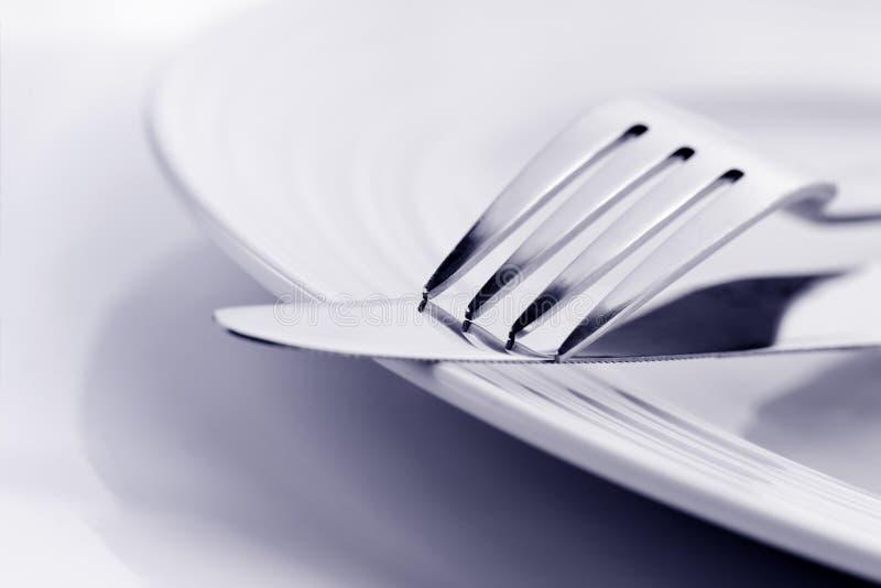 Μαχαίρι και δίκρανο στη μαλακή εστίαση πιάτων στοκ εικόνες