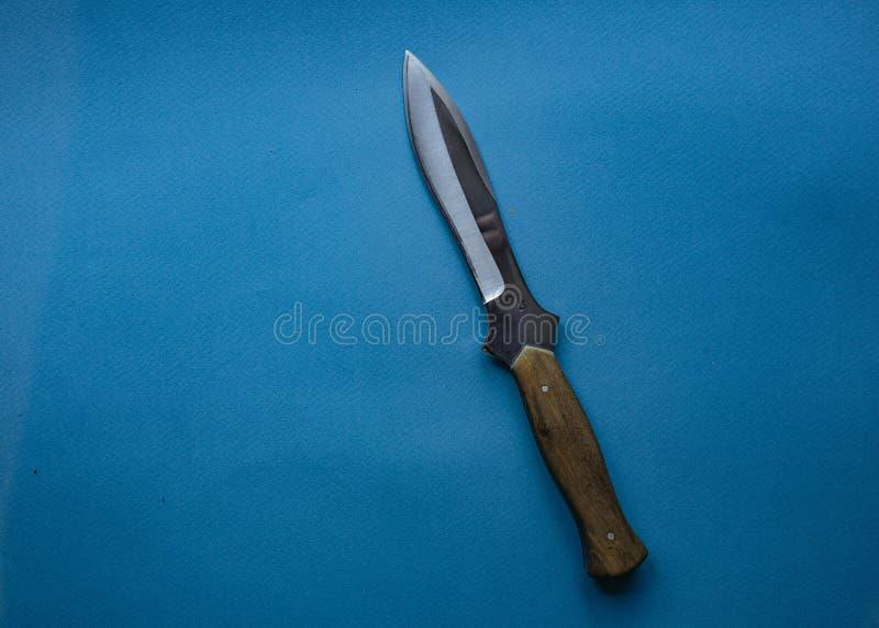 Μαχαίρι κυνηγιού σε ένα μπλε μονοφωνικό υπόβαθρο μονωμένο μαχαίρι στοκ εικόνες με δικαίωμα ελεύθερης χρήσης