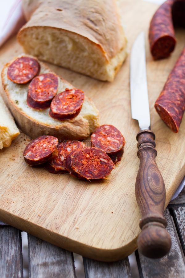 Μαχαίρι, φρέσκα ψωμί και λουκάνικο στον πίνακα στοκ εικόνα