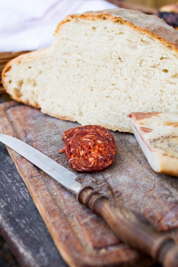 Μαχαίρι, φρέσκα ψωμί και λουκάνικο στον πίνακα στοκ φωτογραφίες