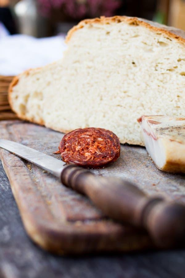 Μαχαίρι, φρέσκα ψωμί και λουκάνικο στον πίνακα στοκ εικόνες με δικαίωμα ελεύθερης χρήσης
