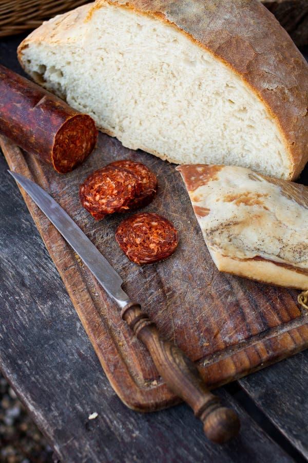 Μαχαίρι, φρέσκα ψωμί και λουκάνικο στον πίνακα στοκ εικόνες