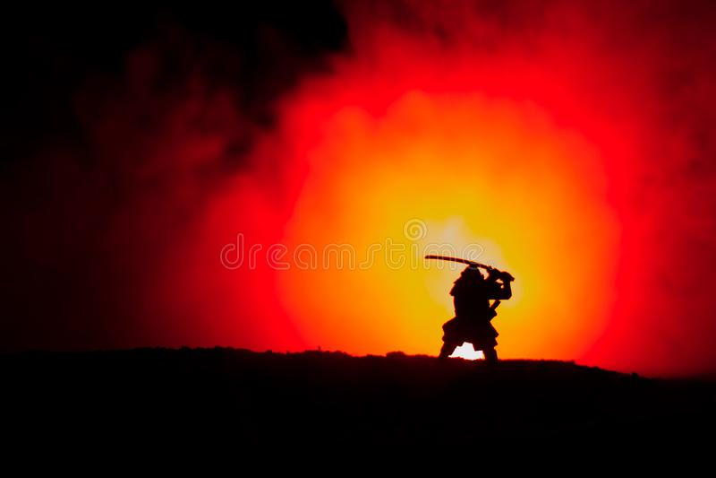 Μαχητής με μια σκιαγραφία ξιφών ένα ninja ουρανού Σαμουράι πάνω από το βουνό με το σκοτεινό τονισμένο ομιχλώδες υπόβαθρο στοκ φωτογραφία