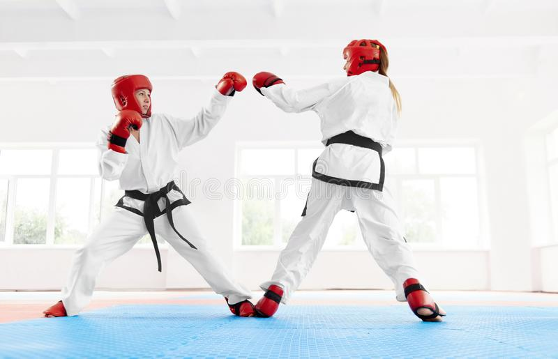 Μαχητής που φορά στον ειδικό κόκκινο προστατευτικό εξοπλισμό για την πάλη, που εγκιβωτίζει από κοινού στοκ εικόνα