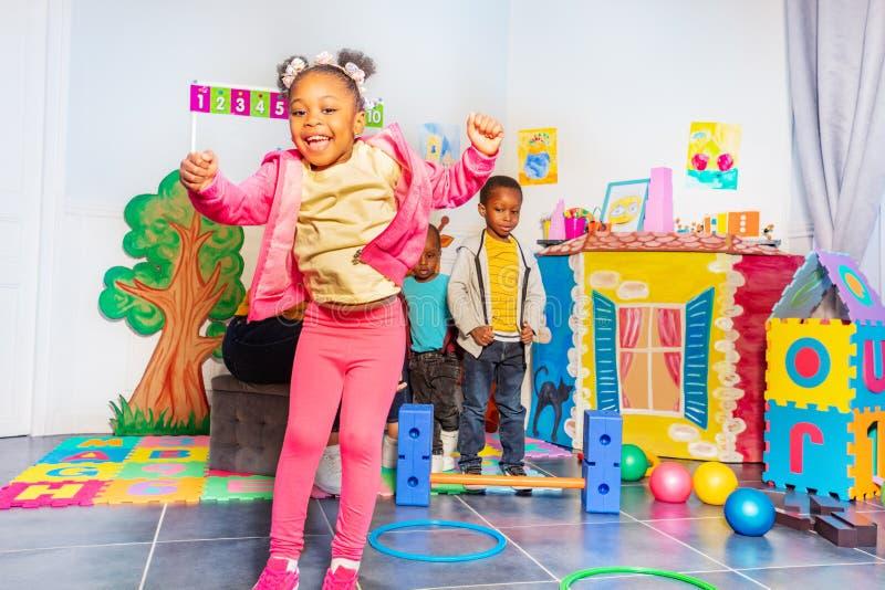 Μαύρα άλματα μικρών κοριτσιών πέρα από τις στεφάνες στον παιδικό σταθμό στοκ εικόνα με δικαίωμα ελεύθερης χρήσης