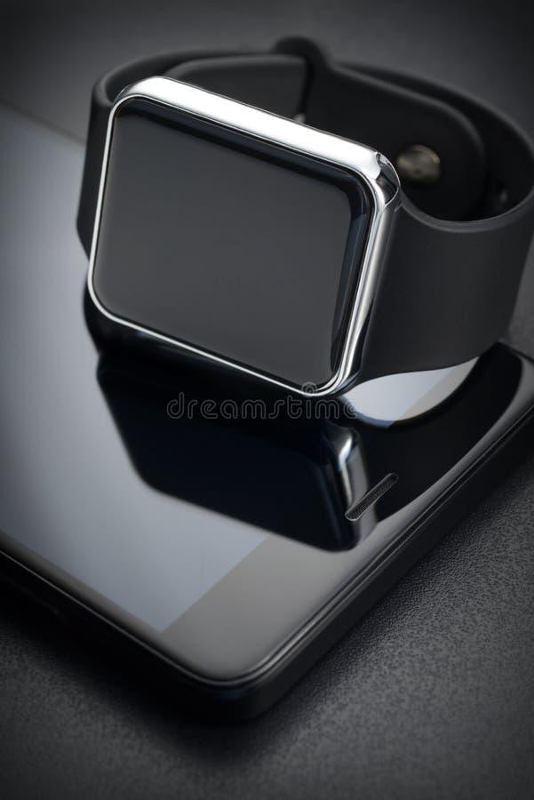 Μαύρα έξυπνα wristwatches και smartphone στοκ φωτογραφία