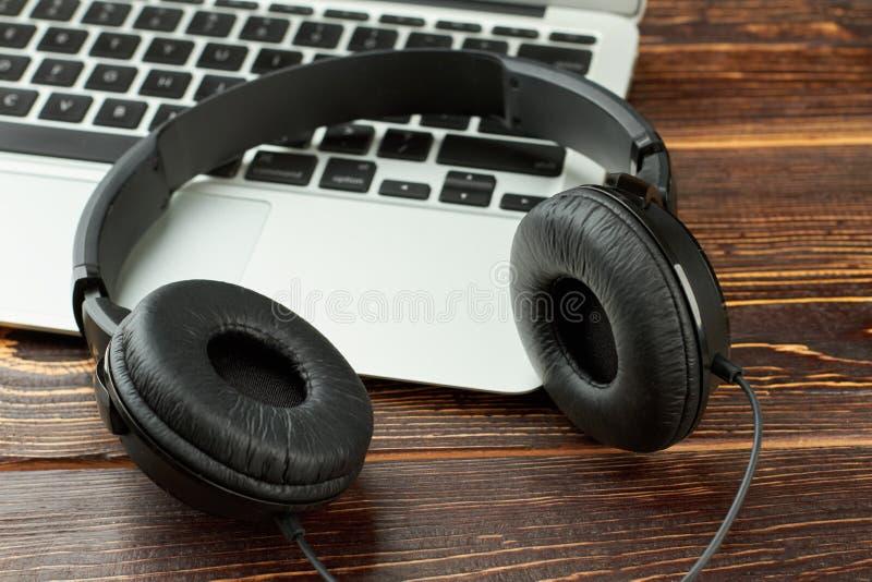 Μαύρα ακουστικά και lap-top δέρματος στοκ εικόνες