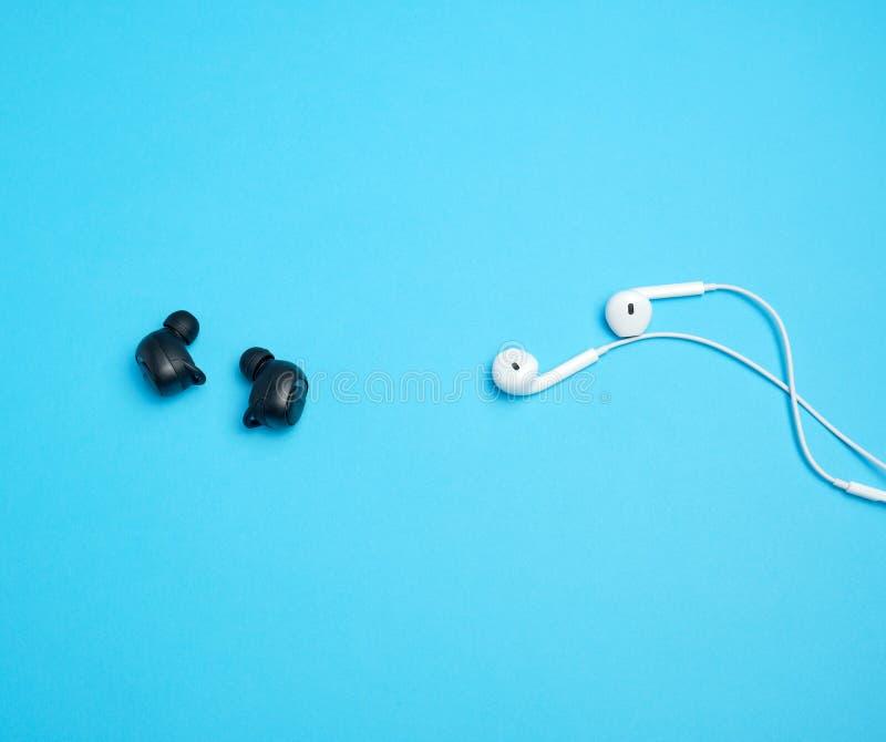 μαύρα ασύρματα και άσπρα ακουστικά με το καλώδιο σε ένα μπλε υπόβαθρο στοκ φωτογραφίες