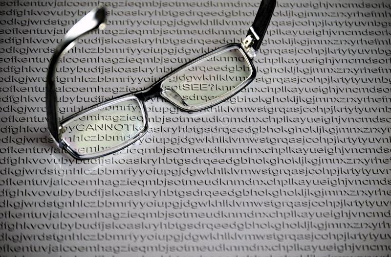 Μαύρα γυαλιά σε ένα υπόβαθρο της Λευκής Βίβλου με τις τυχαίες επιστολές του αγγλικού αλφάβητου, κρυμμένες λέξεις στοκ εικόνα
