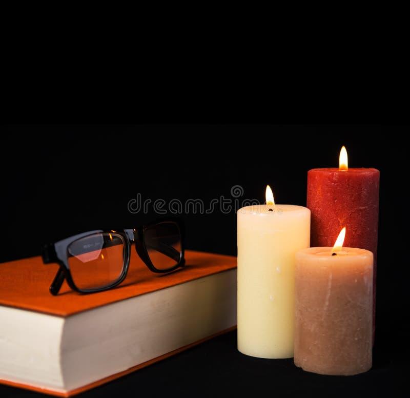 Μαύρα γυαλιά Readig στο πορτοκαλί βιβλίο με τρία καίγοντας κεριά στοκ εικόνα