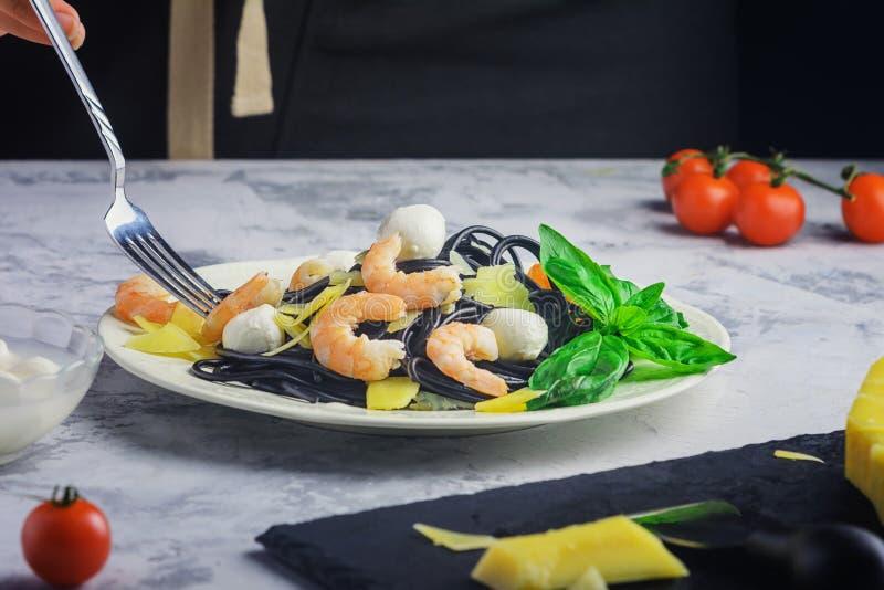 Μαύρα ζυμαρικά με παρμέσαν, γαρίδες και μοτσαρέλα Μακαρόνια με μελάνι Λιχουδιά στοκ εικόνες