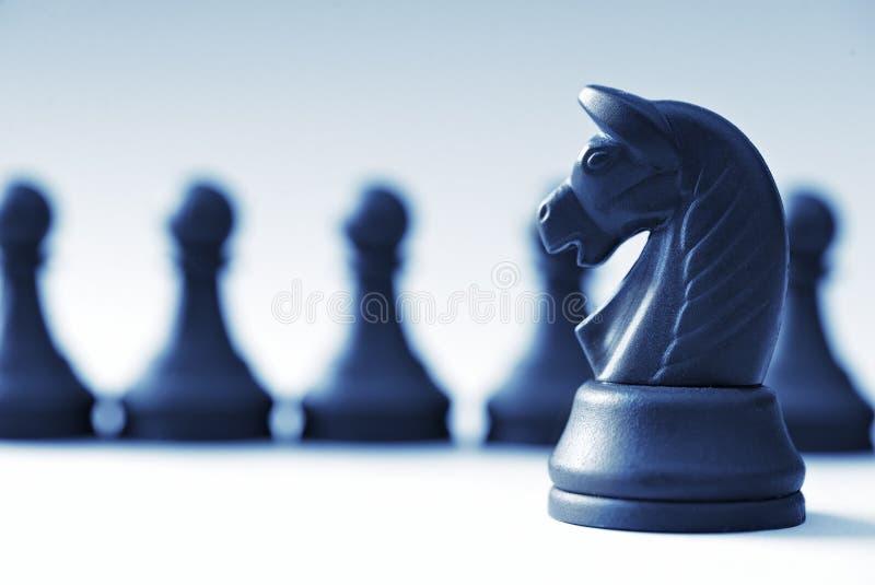 Μαύρα κομμάτια σκακιού και άλογο σε ένα ανοικτό μπλε υπόβαθρο στοκ φωτογραφία με δικαίωμα ελεύθερης χρήσης