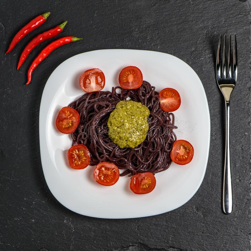 Μαύρα νουντλς με τις ντομάτες και τη σάλτσα pesto στοκ φωτογραφία με δικαίωμα ελεύθερης χρήσης