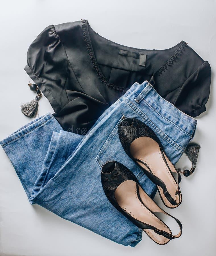 Μαύρα παπούτσια δέρματος, τζιν παντελόνι, μαύρες μπλούζες μεταξιού, γυαλιά ηλίου και σκουλαρίκια μπλε έξυπνη γυναίκα μόδας προσώπ στοκ εικόνα με δικαίωμα ελεύθερης χρήσης