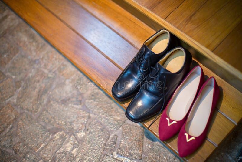 μαύρα παπούτσια νεόνυμφων και κόκκινη θέση παπουτσιών νυφών στο πάτωμα γαμήλια υψηλά τακούνια στον καφετή τάπητα στοκ φωτογραφίες με δικαίωμα ελεύθερης χρήσης