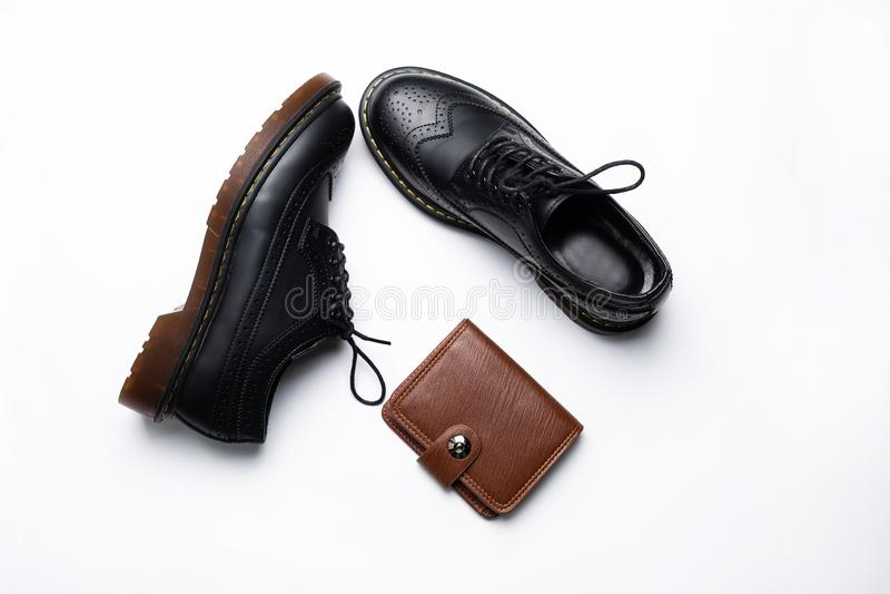 Μαύρα παπούτσια ντέρπι δέρματος με τα πέλματα πολυουρεθάνιου και ένα καφετί πορτοφόλι με ένα κουμπί σε ένα άσπρο υπόβαθρο στοκ εικόνες