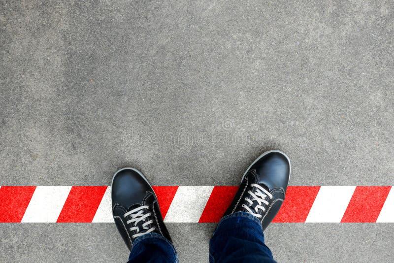 Μαύρα περιστασιακά παπούτσια που στέκονται στην κόκκινη και άσπρη γραμμή στοκ φωτογραφία