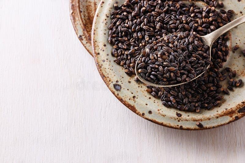 Μαύρα σιτάρια κριθαριού στο κεραμικό πιάτο πέρα από το άσπρο ξύλινο backgroun στοκ εικόνες