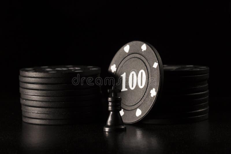 Μαύρα τσιπ βασιλιάδων και πόκερ σκακιού σε ένα σκοτεινό υπόβαθρο στοκ φωτογραφίες