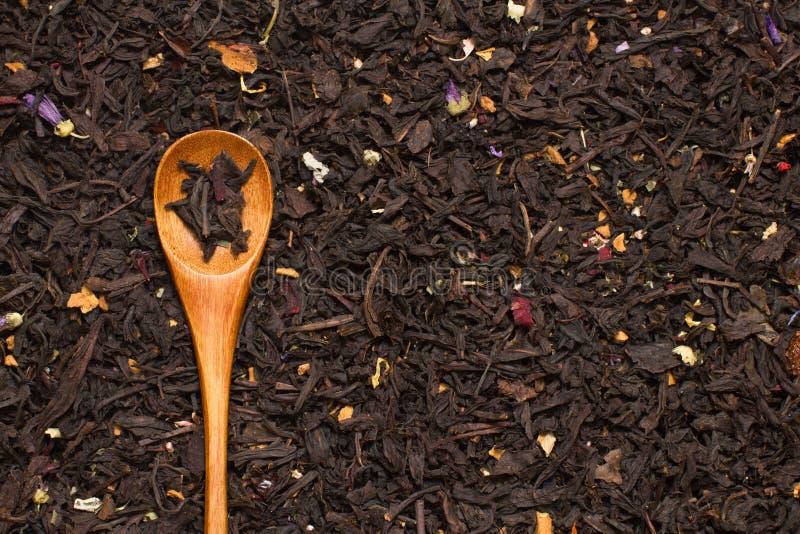Μαύρα φύλλα τσαγιού με τα λουλούδια και φρούτα με το ξύλινο κουτάλι στοκ εικόνα