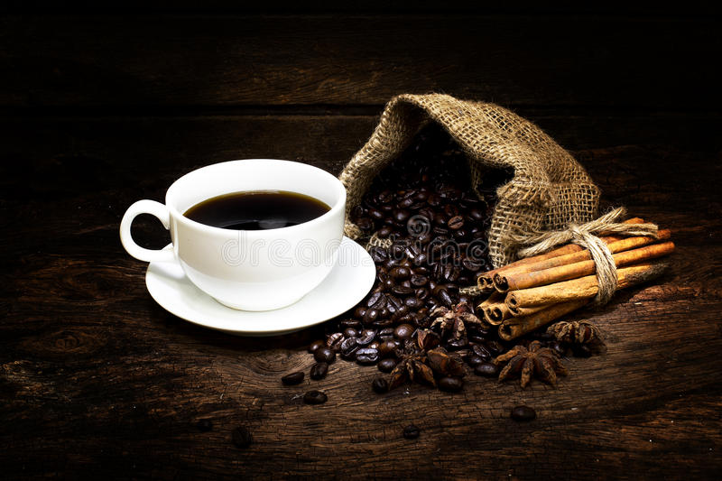 Μαύρα coffe και φασόλια με τα ραβδιά κανέλας στο επιτραπέζιο ξύλο - στοκ εικόνα