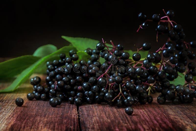 Μαύρα elderberries & x28 Sambucus nigra& x29  με τα φύλλα σε ένα σκοτάδι ξύλινο στοκ φωτογραφίες με δικαίωμα ελεύθερης χρήσης